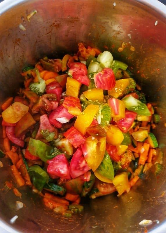 Angedünstetes Gemüse mit geröstetem Tomatenmark in einem Topf.