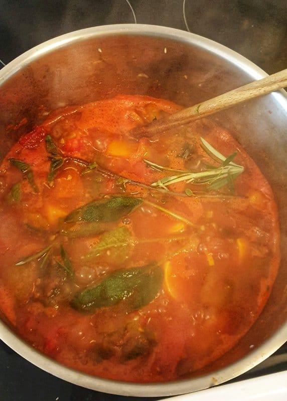 Kochende Suppe mit frischen Gewürzen in einem Topf.