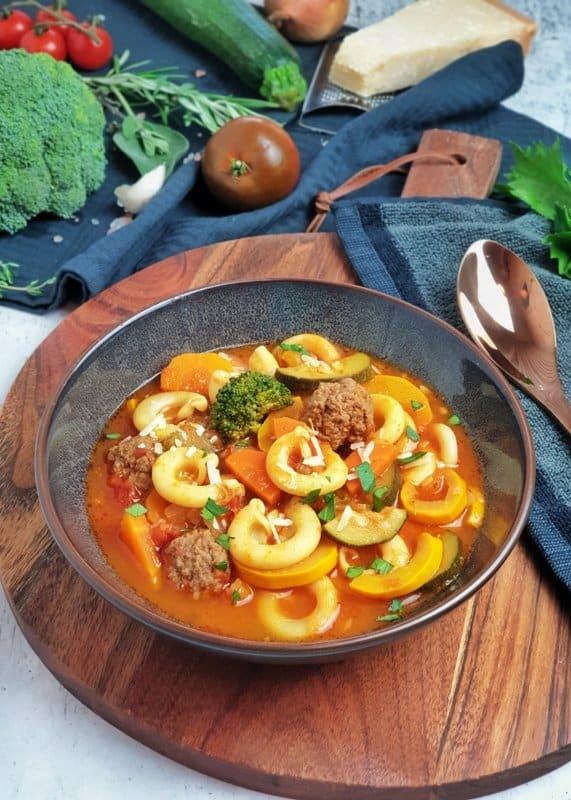 Minestrone - Italienisches Gemüsesuppe mit Hackfleischbällchen in einer braunen Schale angerichtet.
