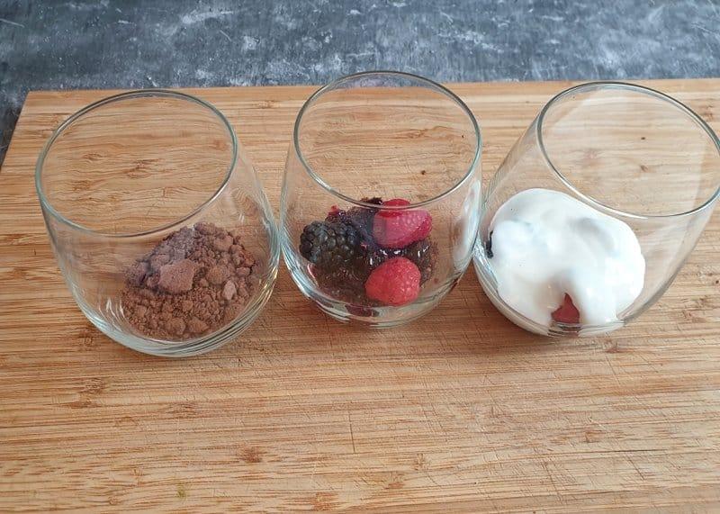3 Gläser auf einem Holzbrett. Glas 1 mit Keksen. Glas 2 Mit Keksen und Beeren, Glas 3 mit Keksen, Beeren und Joghurt.