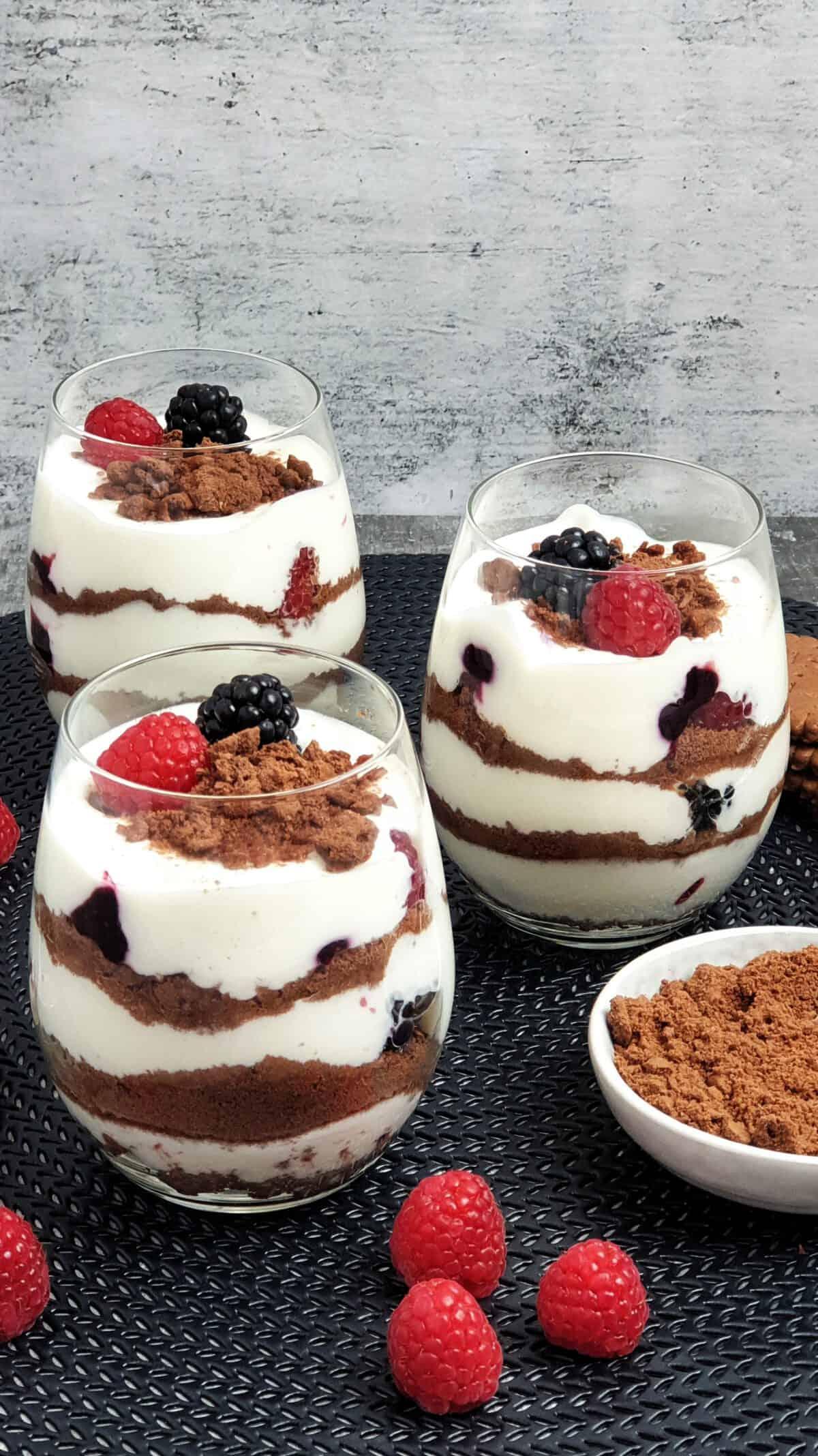 3 Gläser mit Beeren Cheesecake Dessert auf einer schwarzen Unterlage. Daneben Deko.