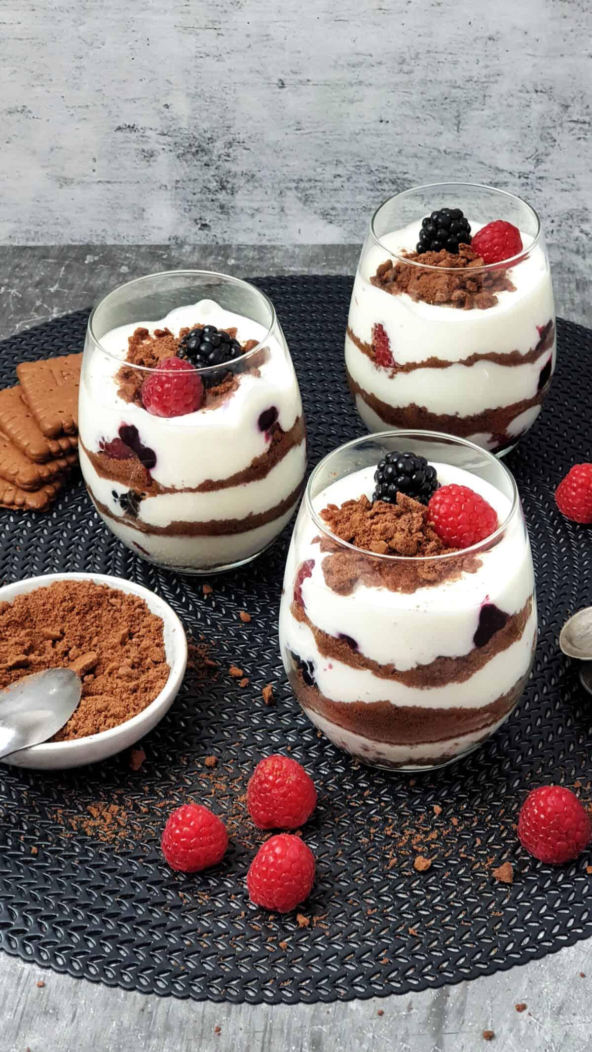 3 Gläser mit Joghurt Dessert und Früchten auf einer schwarzen Unterlage. Daneben Deko.