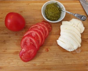 Auf einem Schneidebrett Tomaten und Mozzarella Scheiben, daneben eine Schale mit grünem Pesto.