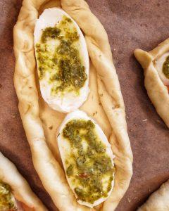 Auf einem Backpapier ein Teigschiffchen gefüllt mit Mozzarella und Pesto.