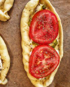 Hefeteig Schiffchen gefüllt mit Tomate und Mozzarella auf Backpapier.