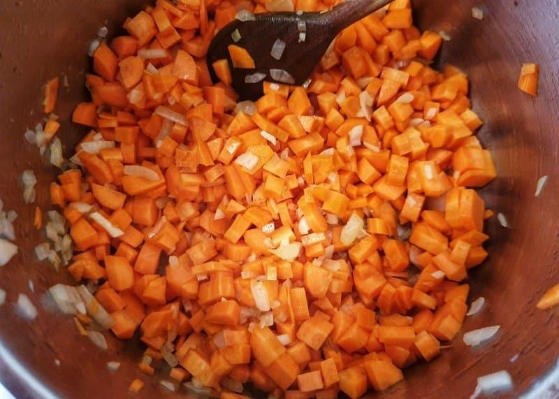 In einem Topf angedünstete Möhren Würfel mit Zwiebeln.