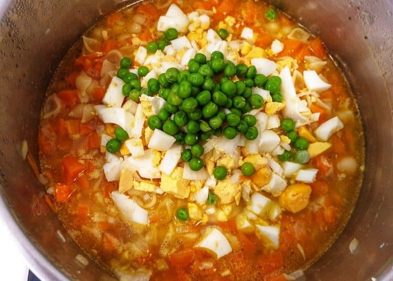 In einem Topf eine rote Suppe mit Möhren, Ei, Nudeln und Erbsen.
