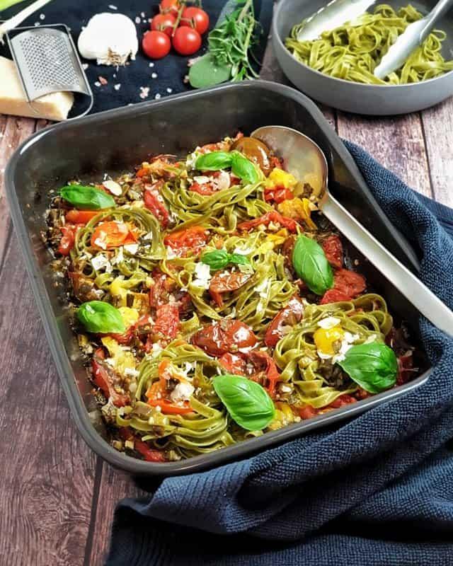 Pasta mit Tomatensugo aus dem Backofen angerichtet in einer dunklen Auflaufform mit Parmesan und Basilikum garniert.