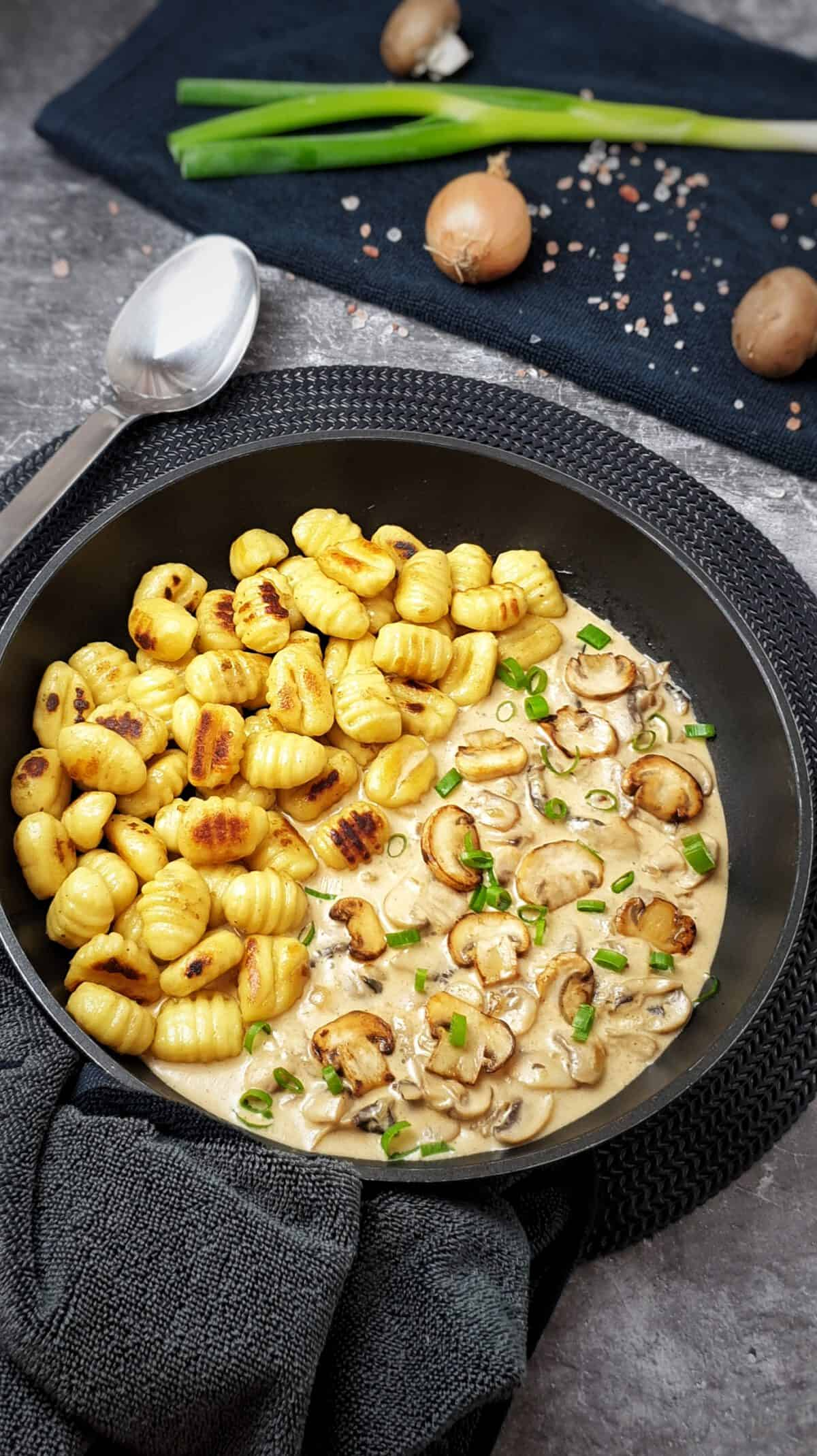 In einer Pfanne nebeneinander angerichtet gebratene Gnocchi und Rahmsoße mit Champignons.