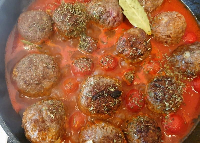 Hackfleischbällchen in Tomatensoße in einer Pfanne.