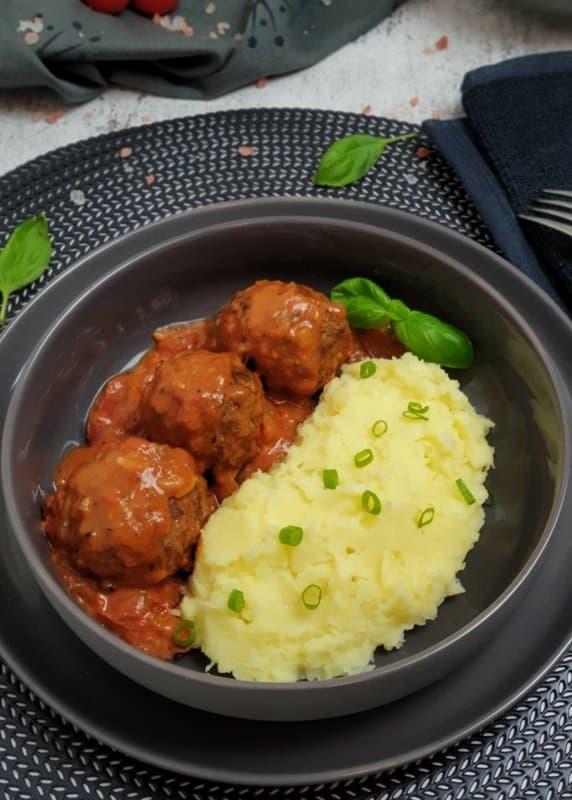 Hackfleischbällchen in Tomatensoße mit Kartoffelstampf in einer grauen Schale.