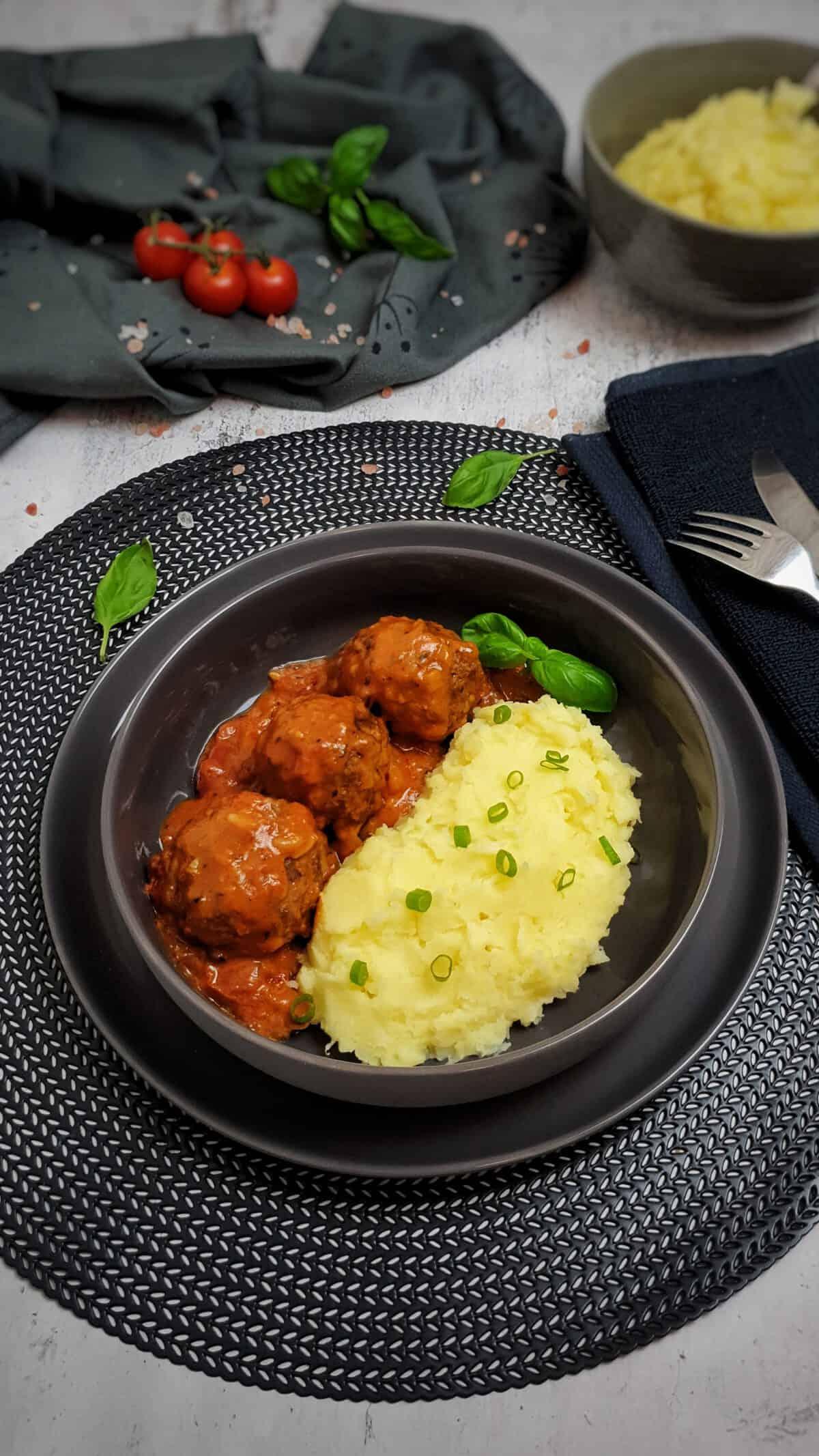 In einer grauen Schale Hackfleischbällchen in Tomatensoße mit Kartoffelpüree.
