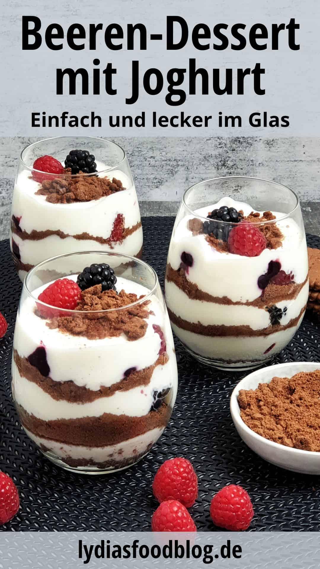 3 Gläser mit Beeren-Cheesecake Dessert auf einer schwarzen Unterlage. Daneben Deko.