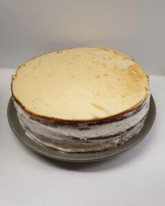 Eine geschichtete Torte aus mehreren Böden mit einer Sahnecreme dazwischen.