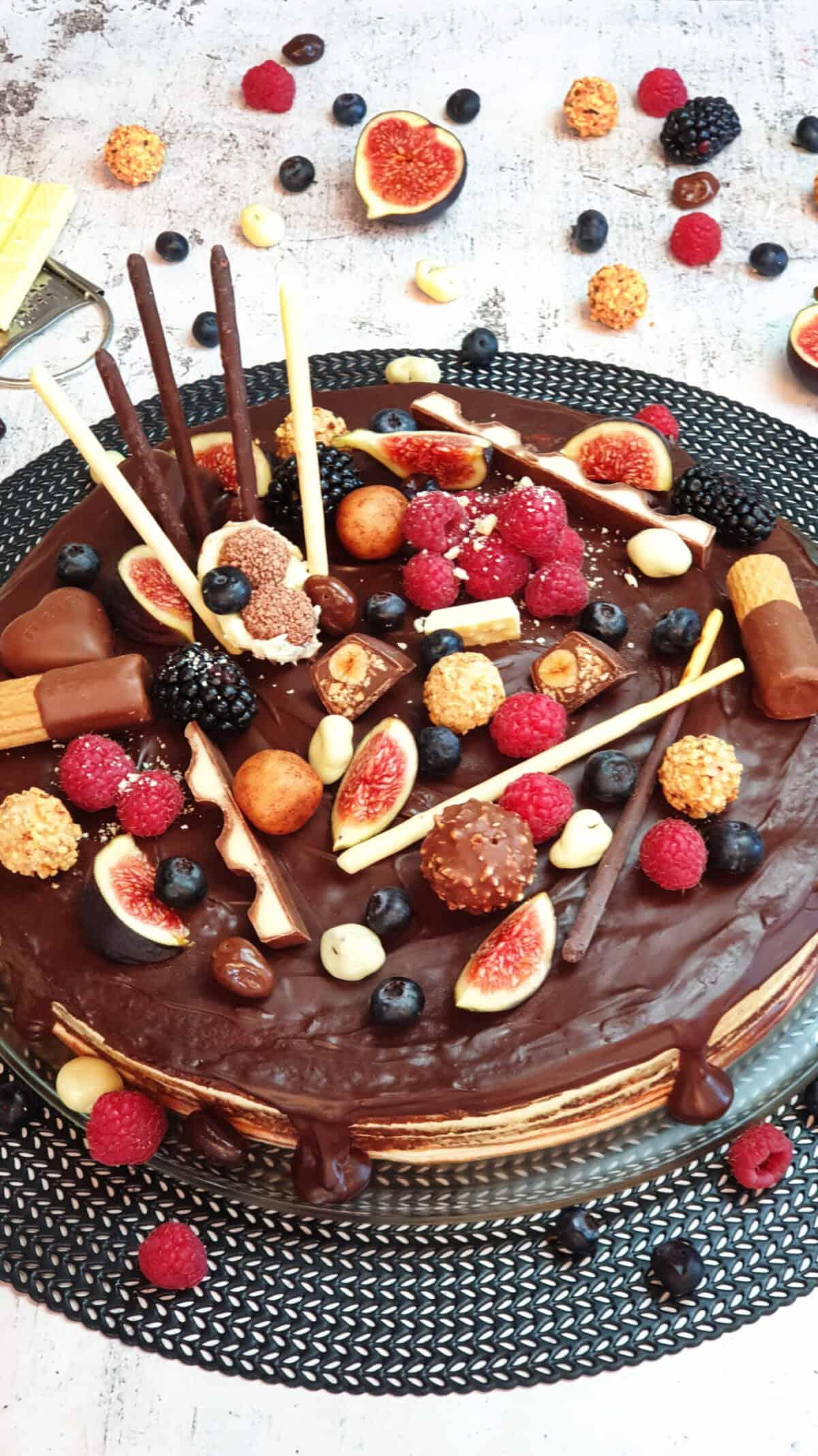 Eine Candy Cake Torte verziert mit Früchten und Schokolade. Im Hintergrund Deko aus Schokoriegeln und Feigen.