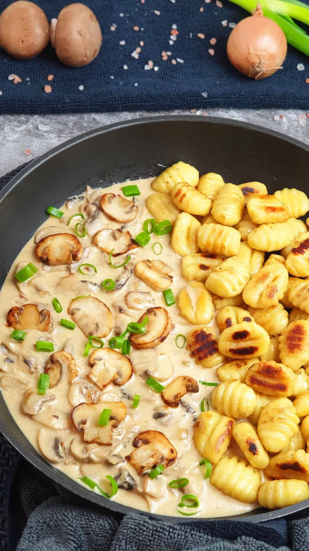 In einer Pfanne angerichtet gebratene Gnocchi mit cremiger Pilz-Rahm-Soße. Mit Petersilie bestreut. Im Hintergrund Deko.