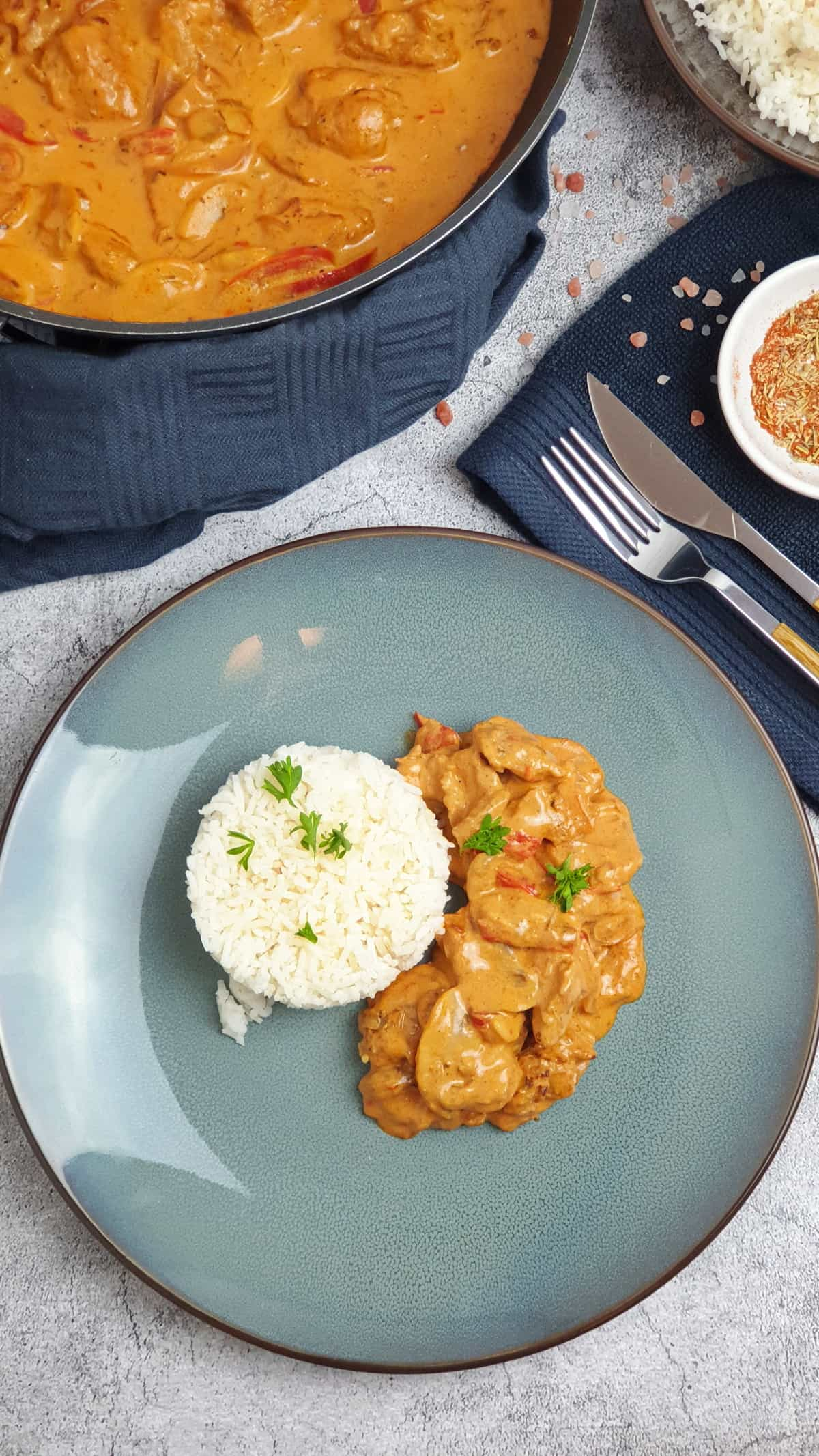 Gyros Geschnetzeltes mit Schmand-Soße und Reis auf einem blauen Teller.