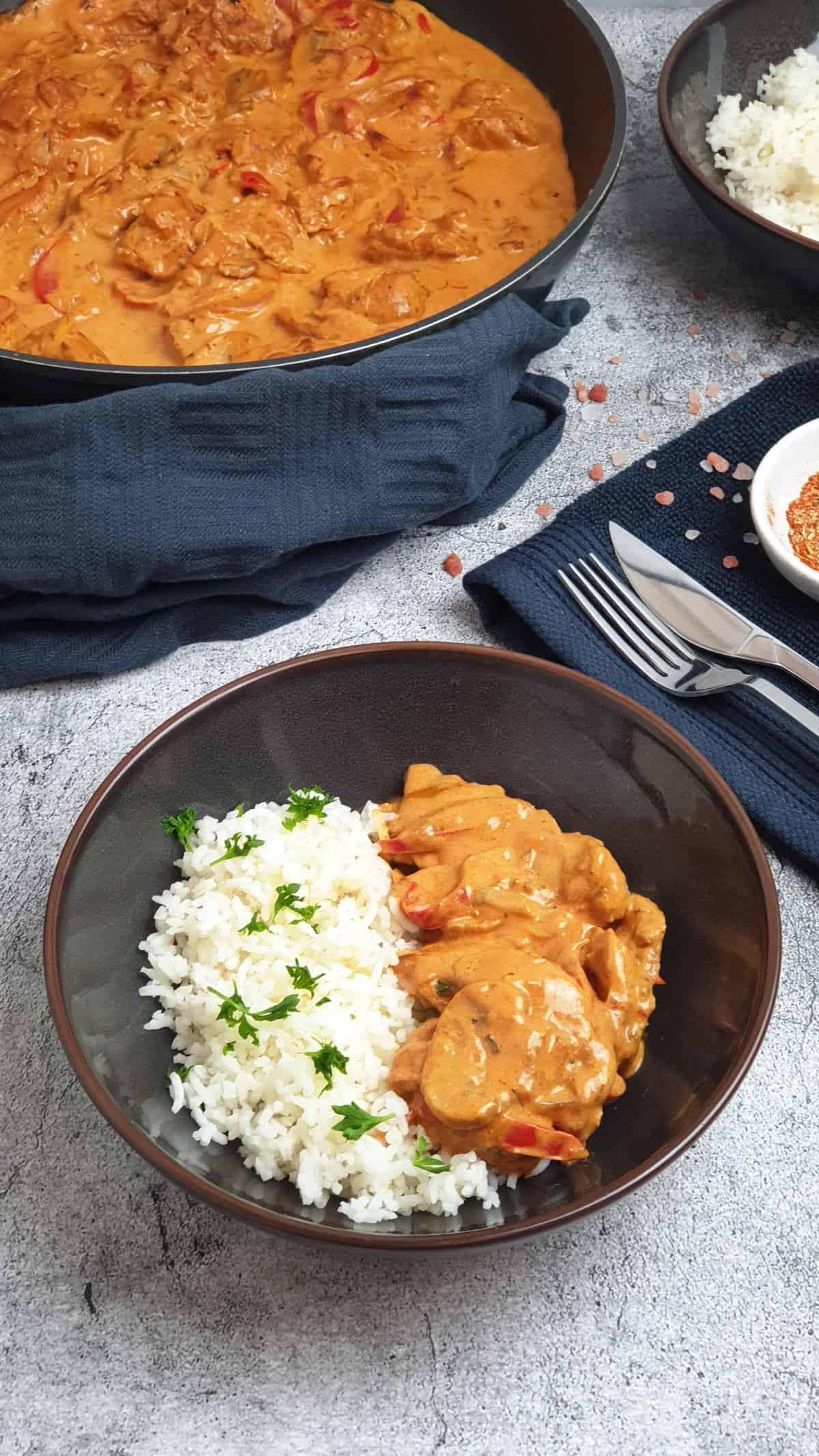 Geschnetzeltes mit Reis in einer braunen Schale. Im Hintergrund Deko.