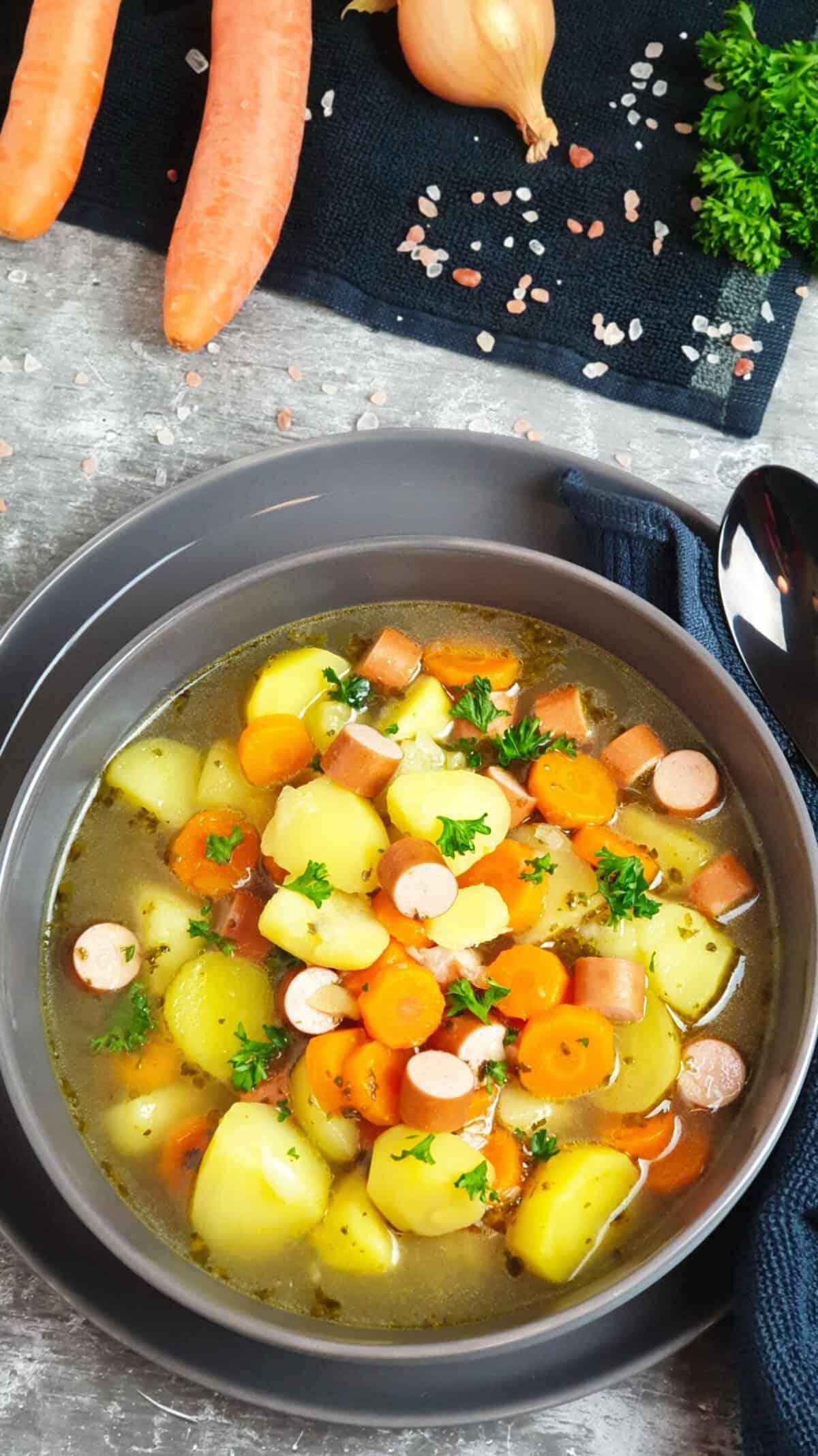 In einer grauen Schale angerichtet Kartoffel Möhren Suppe mit Würstchen. Mit Petersilie bestreut. Im Hintergrund Deko.
