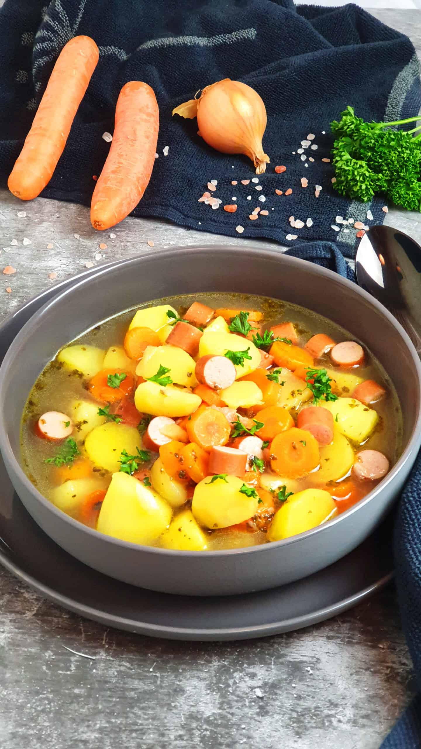 In einer grauen Schale eine Kartoffel-Möhren Suppe mit Wiener Würstchen. Mit Petersilie bestreut. Im Hintergrund Deko.