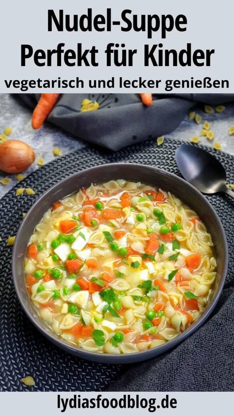 In einer dunkelgrauen Schale angerichtet eine bunte vegetarische Nudelsuppe mit Gemüse.