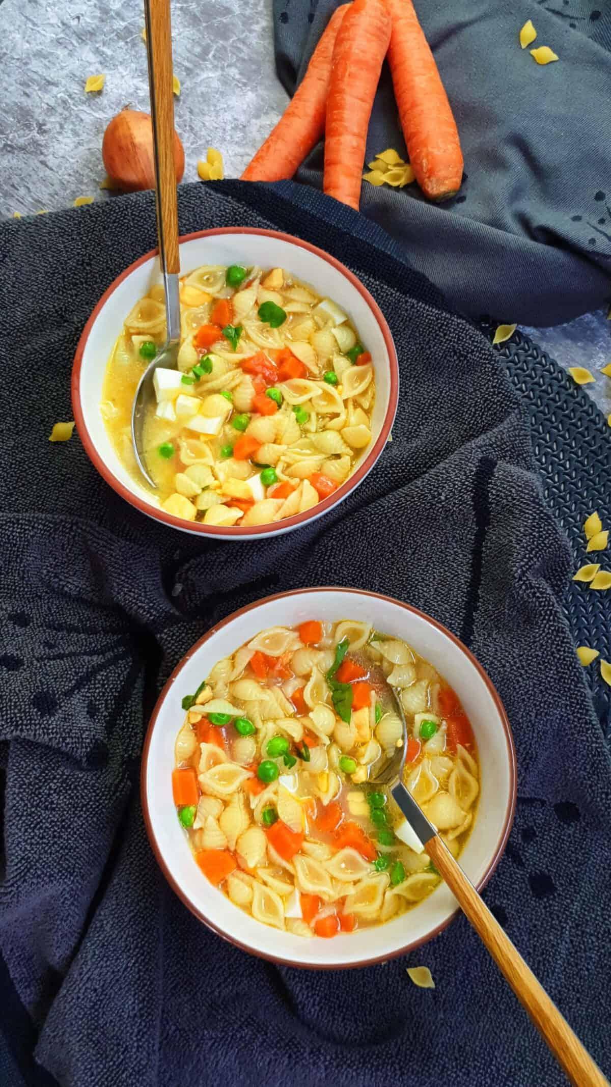In zwei weißen Schalen serviert, eine bunte Nudelsuppe mit Gemüse. Im Hintergrund Deko.