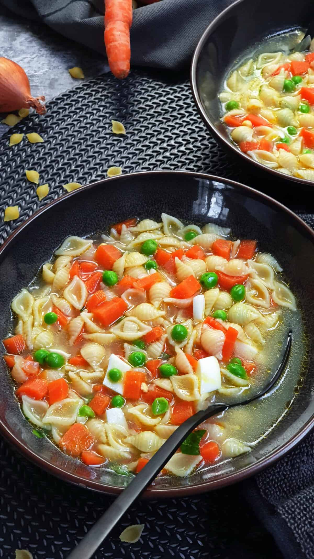 In einer braunen Schale eine Nudelsuppe mit buntem Gemüse und gekochtem Ei. Im Hintergrund Deko.