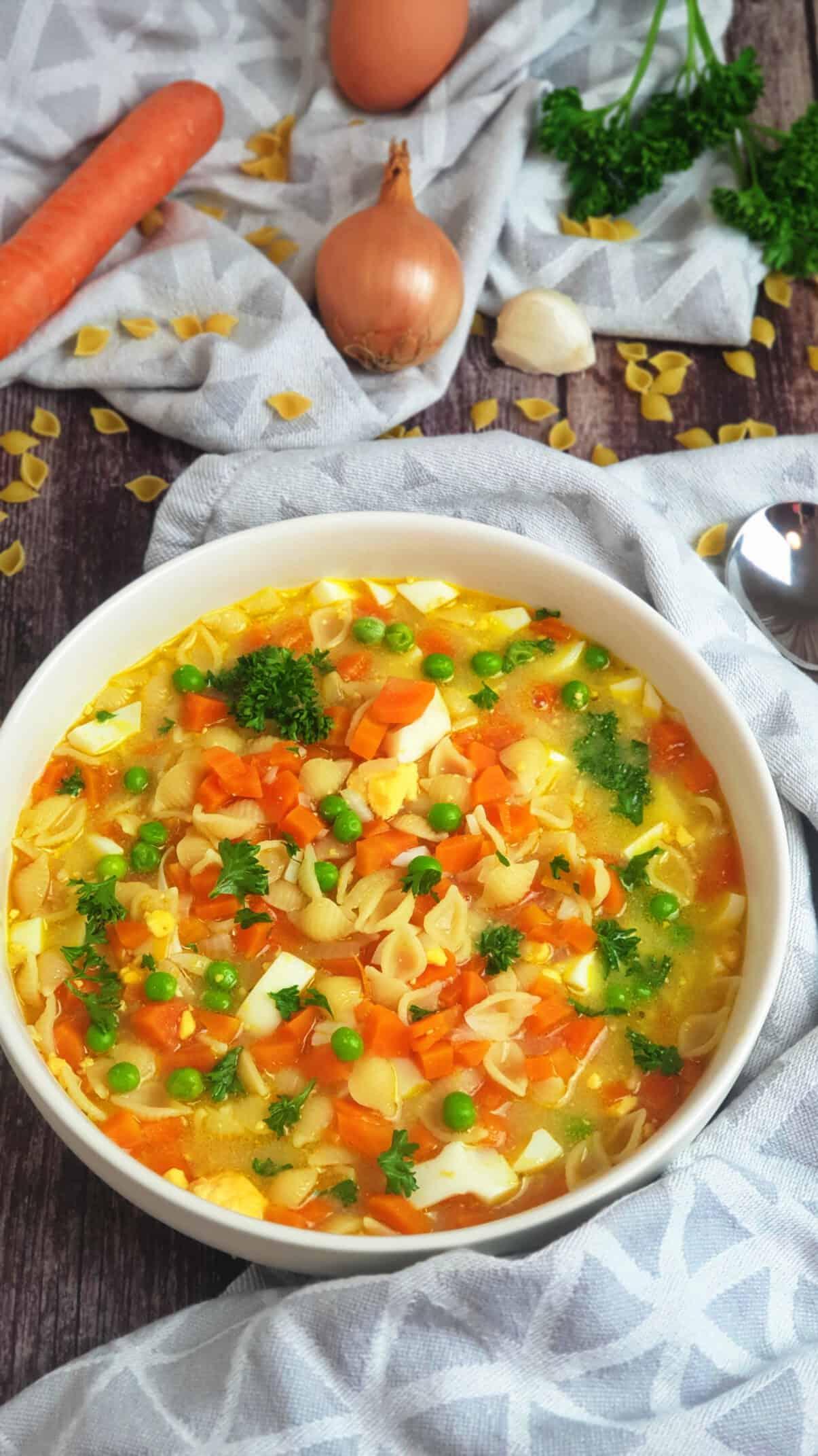 In einer weißen Schale eine Nudelsuppe mit buntem Gemüse und gekochtem Ei. Im Hintergrund Deko.