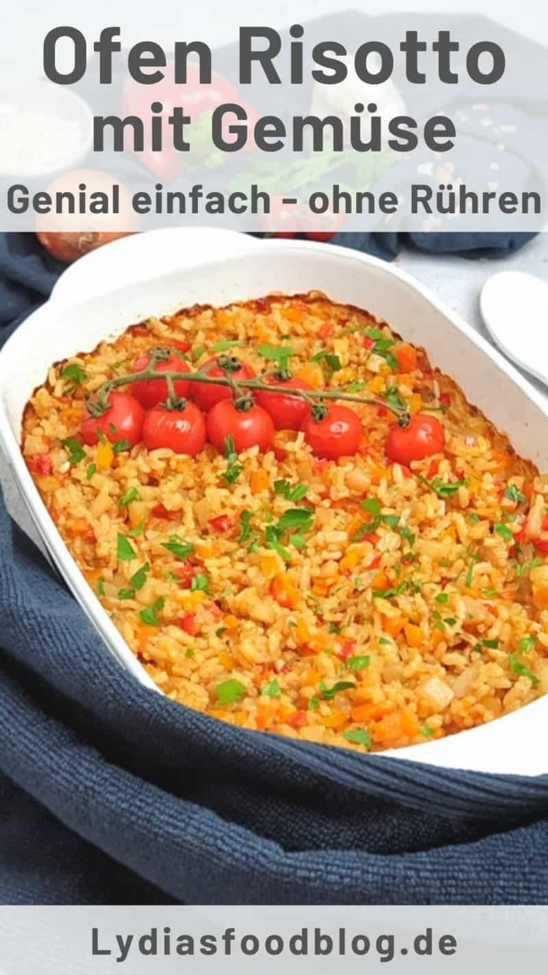 In einer weißen Auflaufform, ein buntes Ofen Risotto mit Möhren, Kohlrabi und Tomaten, dekorativ fotografiert. Im Vordergrund ein dunkles Handtuch um die Auflaufform drapiert.