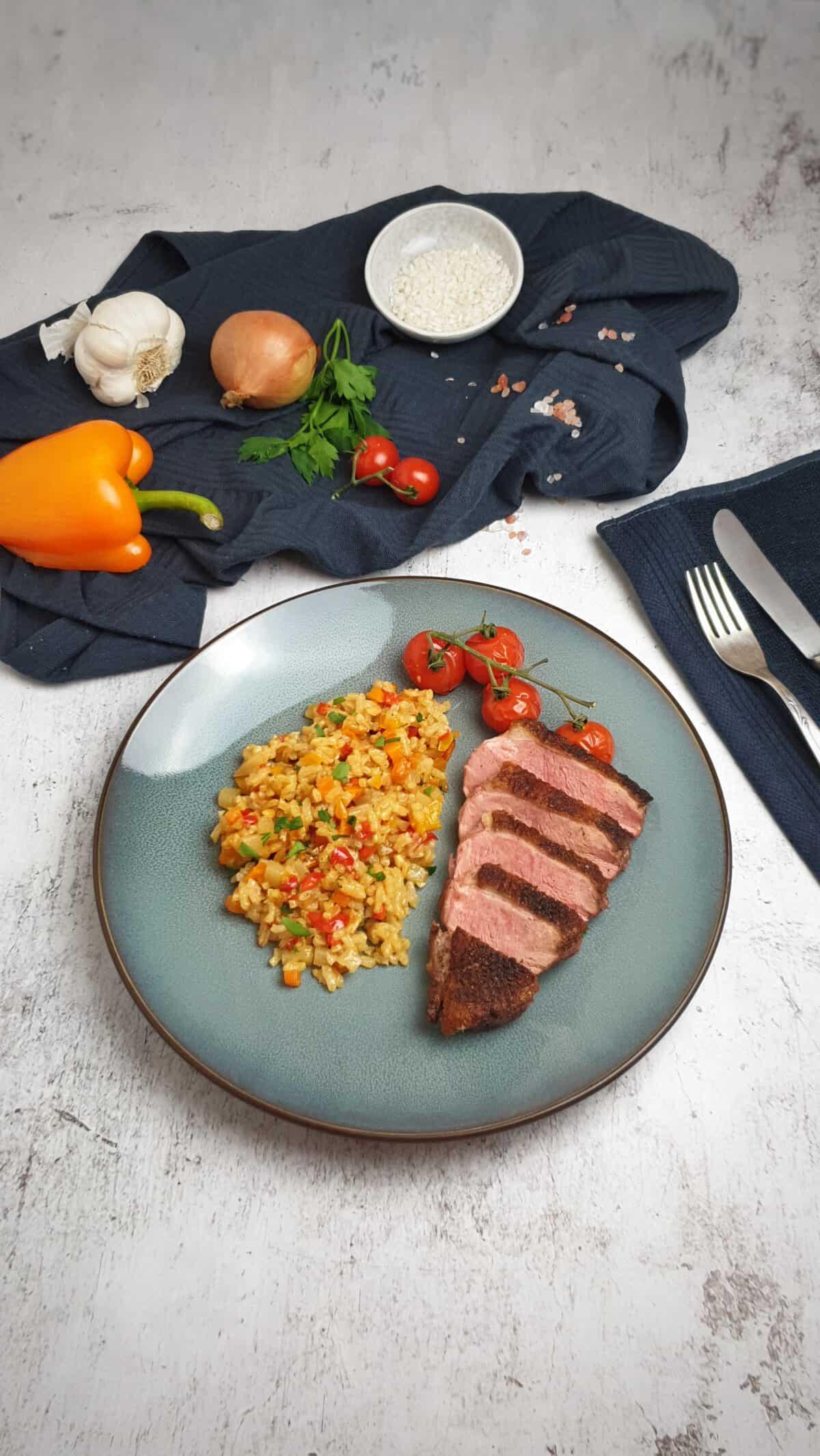 Auf einem blauen Teller angerichtet Ofen Risotto mit Entenbrust. Im Hintergrund Deko.