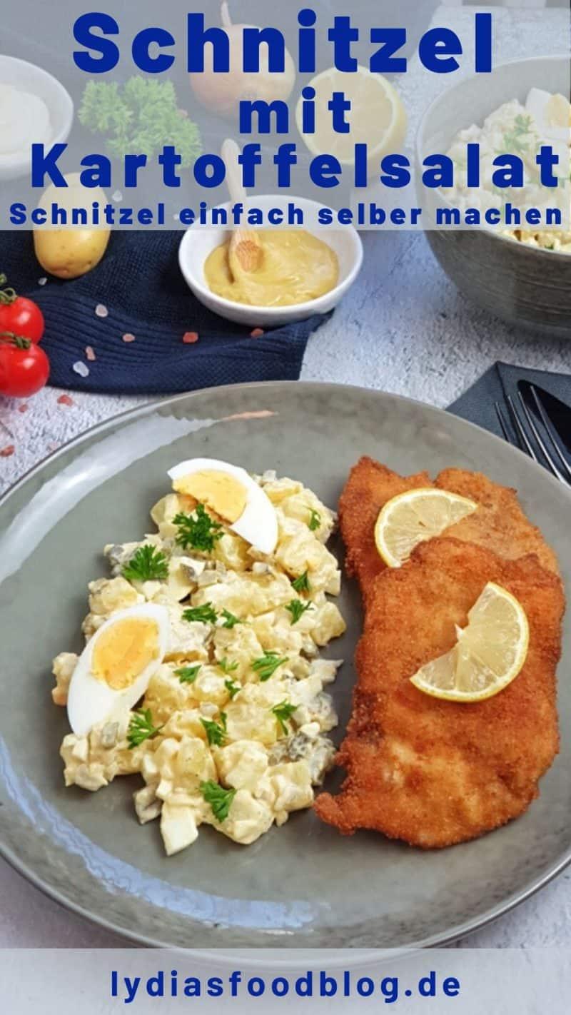 Auf einem dunklen Teller angerichtet Kartoffelsalat mit einem Schnitzel. Auf dem Schnitzel eine Scheibe Zitrone, auf dem Kartoffelsalat mit Mayonnaise und Ei, mit Petersilie bestreut. Im Hintergrund eine Schale mit Kartoffelsalat auf einem Küchenhandtuch dekorativ angerichtet.