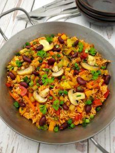 Gemüse-Reis-Pfanne in einer gußeisernen Pfanne angerichtet und mit Petersilie bestreut.