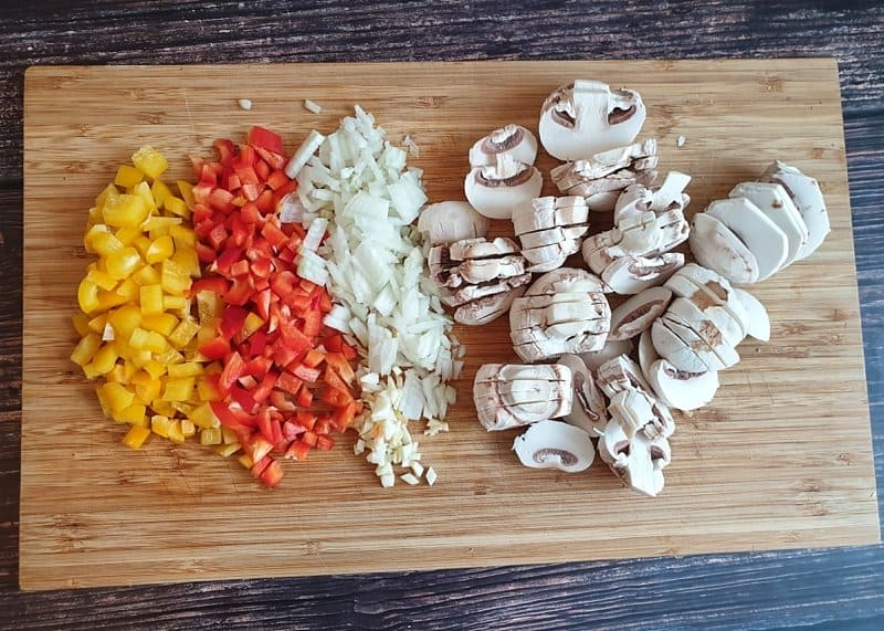 Auf einem Schneidebrett klein geschnittenes Gemüse für die Pizzasuppe.