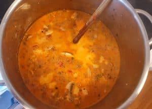 In einem Topf eine Suppe mit Hackfleisch und Pilzen.