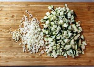 Zucchini und Zwiebeln in Würfel geschnitten auf einem Schneidebrett.