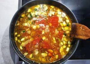 Gemüse mit Tomatenmark und Brühe in der Pfanne.