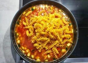 Die Nudeln und alle anderen Zutaten für das Gericht sind in der Pfanne.