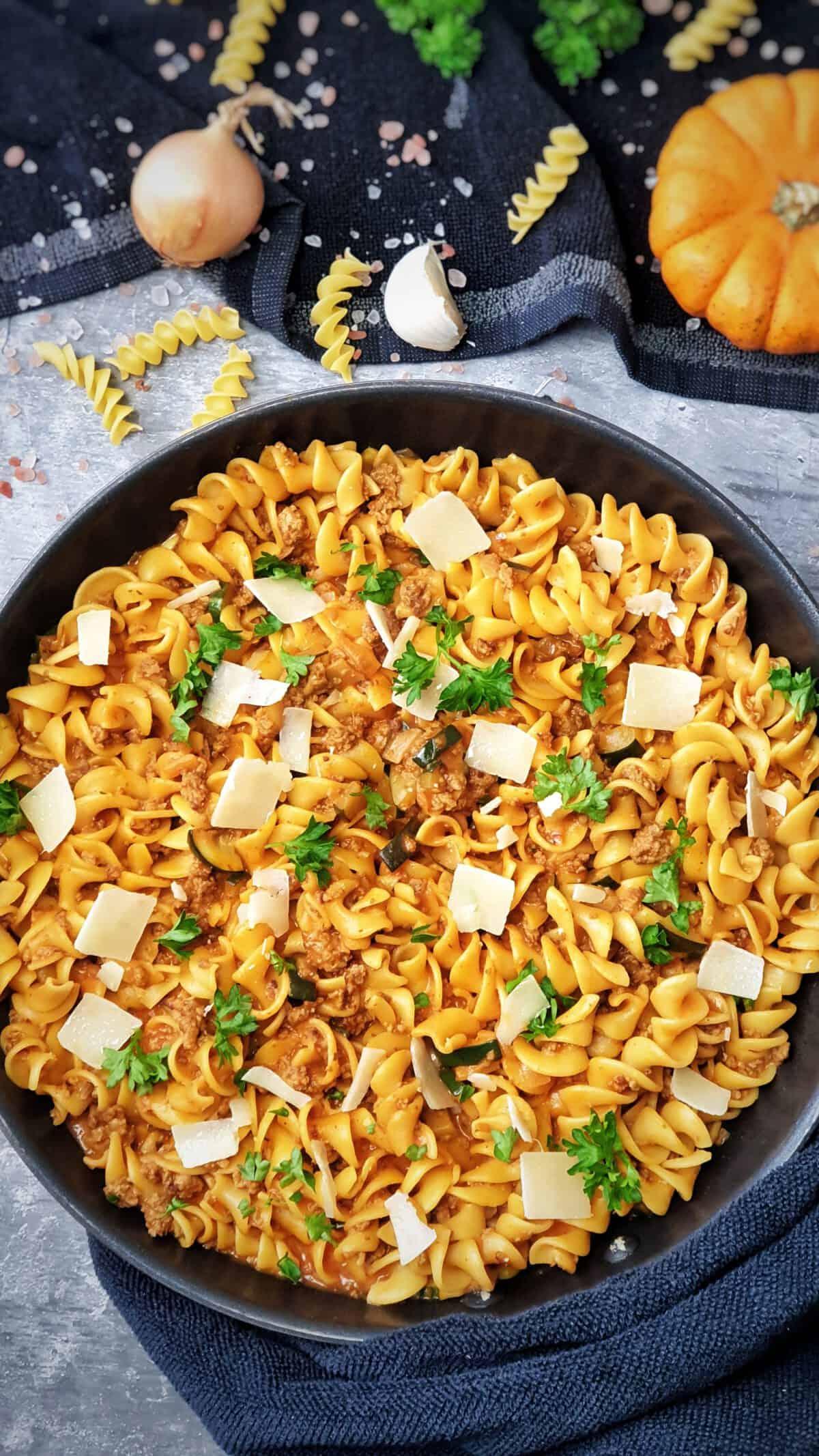 In einer Pfanne Nudel-Pfanne mit Zucchini und Hackfleisch. Mit Parmesan Hobel und Petersilie bestreut. Im Hintergrund Deko.