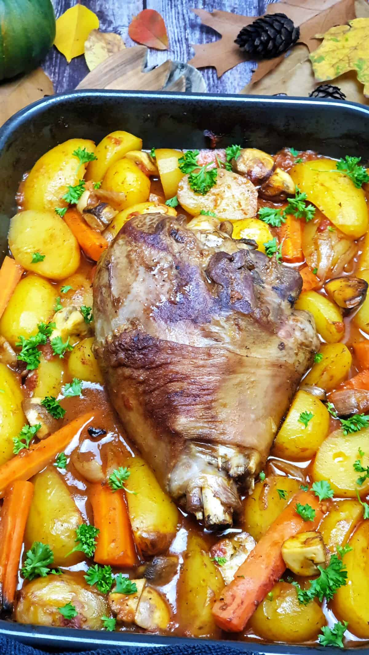 Putenkeule auf Kartoffel-Möhren-Gemüse aus dem Ofen in einer dunklen Auflaufform. Mit Petersilie bestreut. Im Hintergrund Deko.