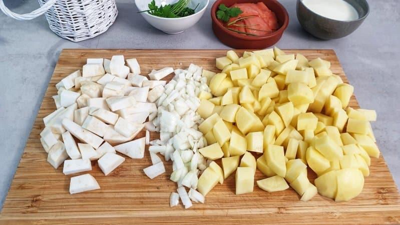 Die Kartoffeln schälen und in Würfel schneiden. Den Sellerie ebenfalls schälen und in Würfel schneiden. Die Zwiebel schälen grob klein schneiden