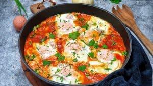 Shakshuka - pochierte Eier in Tomatensoße in einer Pfanne angerichtet und mit Petersilie und Schnittlauch bestreut.