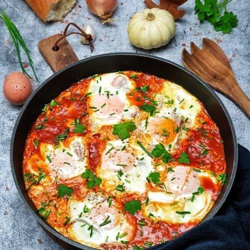 Shakshuka, pochierte Eier in Tomatensoße in einer Pfanne angerichtet. Im Hintergrund herbstliche Deko.