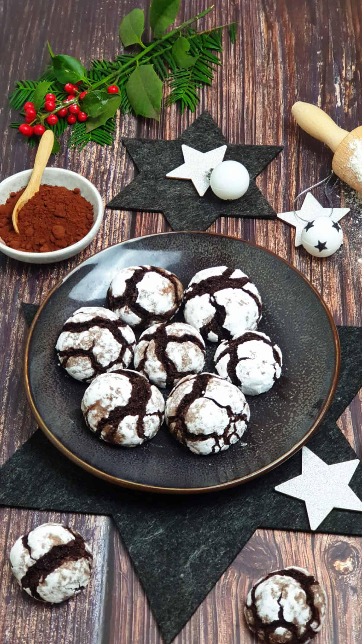 Auf einem braunen Teller weiße Crinkle-Cookies. Im Hintergrund Deko.