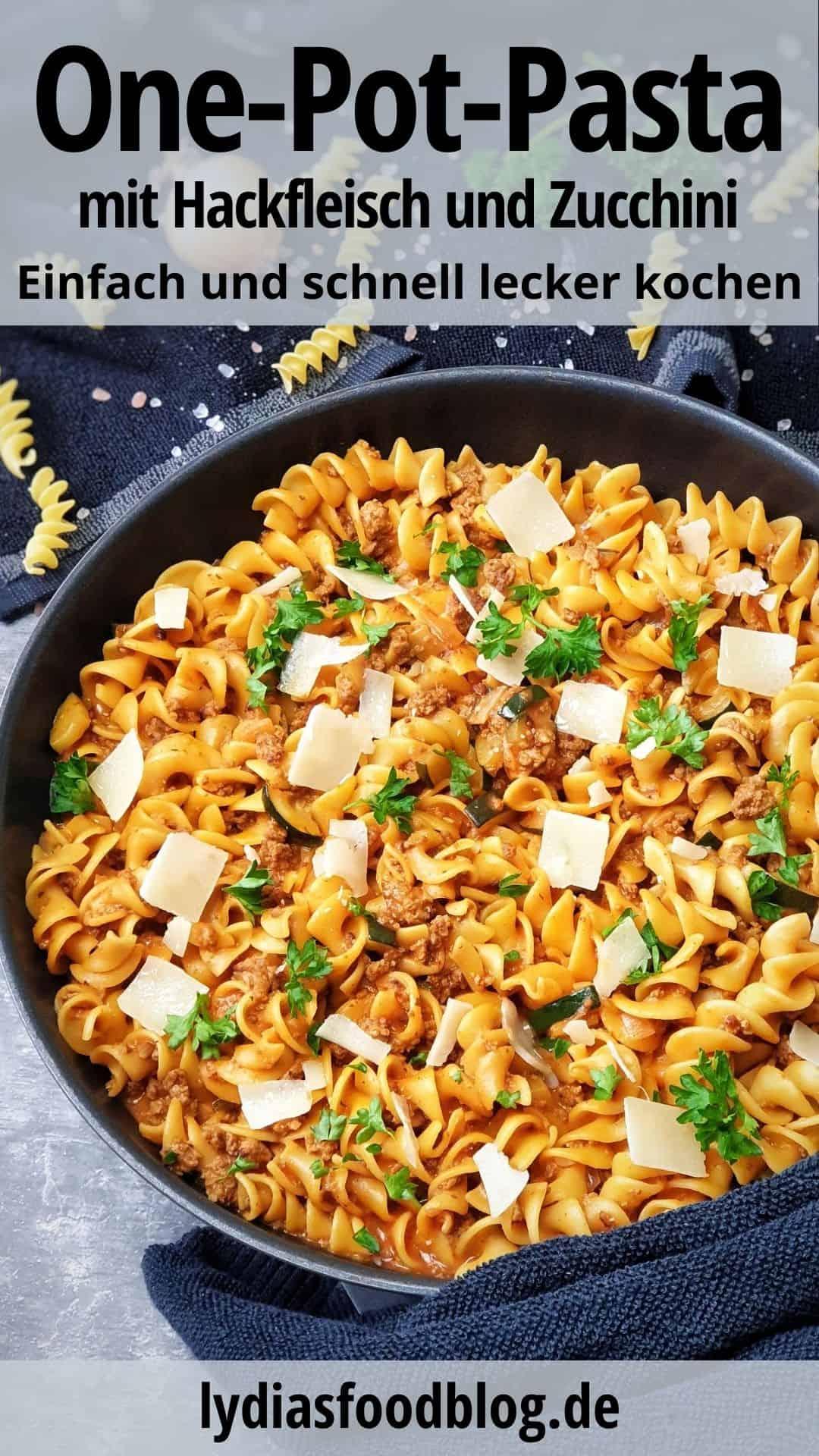 In einer Pfanne Nudel-Hackfleisch-Pfanne mit Zucchini. Mit Parmesan Hobel und Petersilie bestreut. Im Hintergrund Deko.