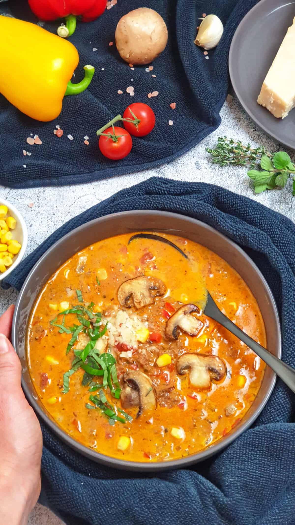In einer grauen Schale angerichtet eine Low Carb Pizzasuppe mit Hackfleisch und Champignons. Mit Parmesan und frischen Kräutern serviert.