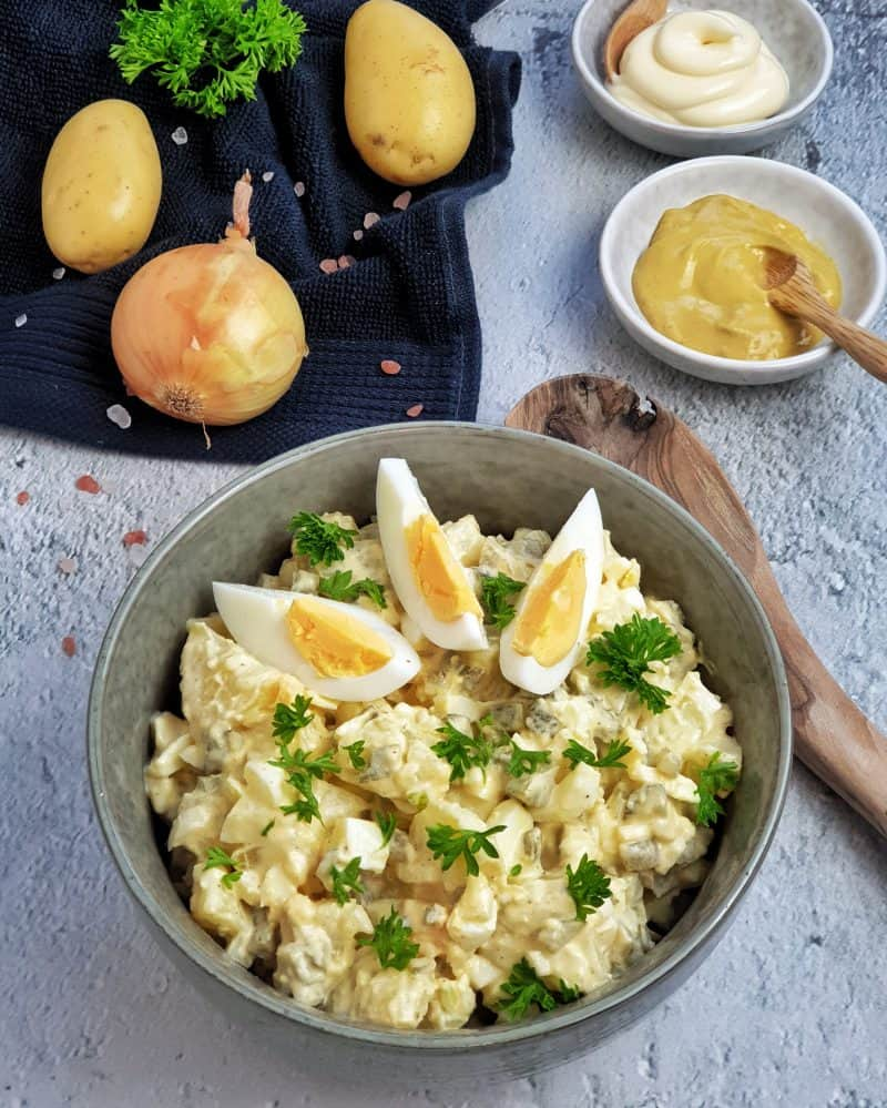 Den Kartoffelsalat mit etwas frischer Petersilie bestreut servieren
