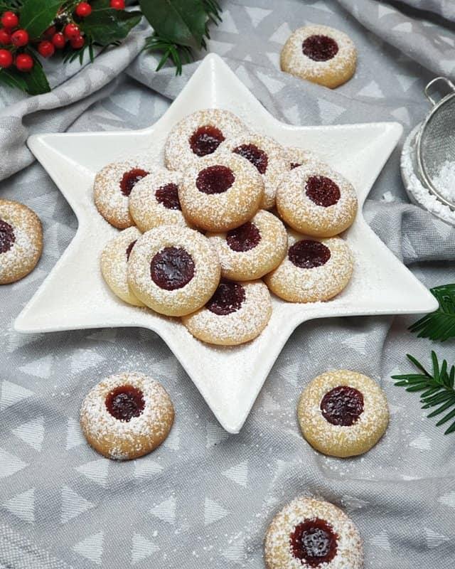 Engelsaugen oder auch Husarenkarpfen genannt sind butterweiche Kekse mit Konfitüre. Angerichtet auf einem sternförmigen Teller mit Weihnachtsdeko, in Form von Tannenzweigen im Hintergrund