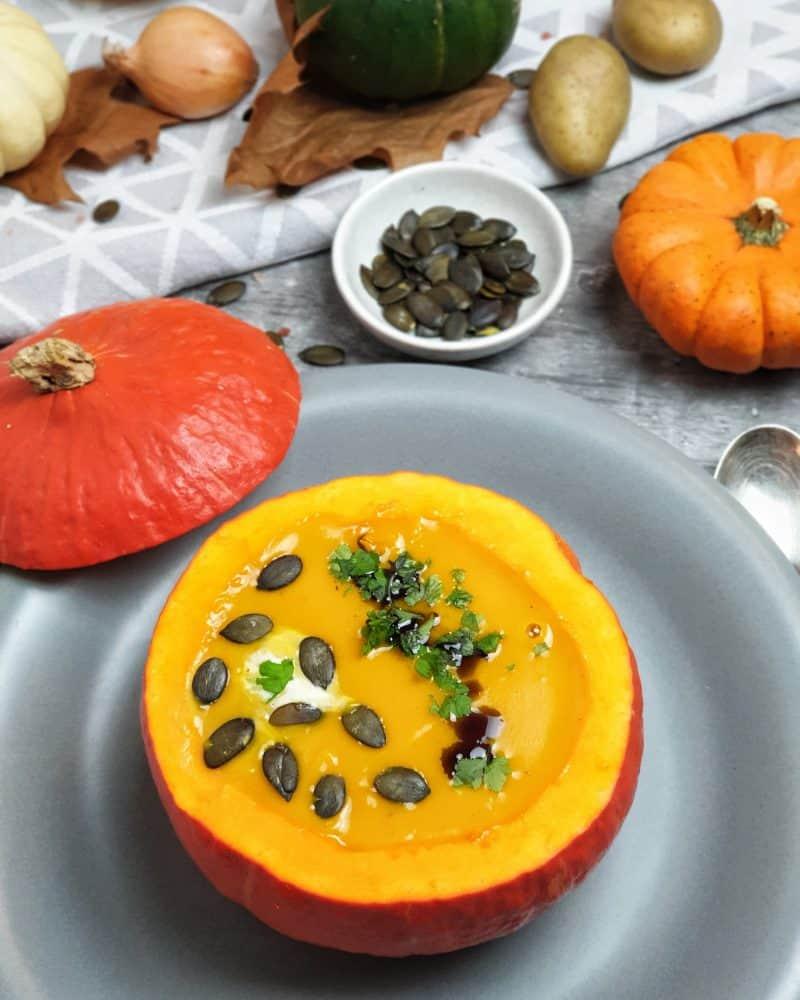 Die Kürbis-Suppe mit Kokosmilch wird mit Kürbiskernöl, Petersilie und Kürbiskernen serviert. Auch in einem ausgehöhlten Kürbis sieht das klasse aus.
