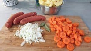 Auf einem Schneidebrett die Zutaten für Kartoffel-Möhren-Eintopf mit Rindswurst.