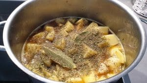 In einem Topf Kartoffeln mit Gewürzen und Lorbeerblatt in Brühe.